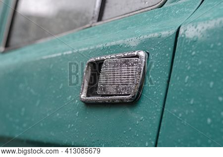 Car Exterior Door Handle With Rain Drops. A Fragment Of A Door And A Chrome-plated Handle Of A Green