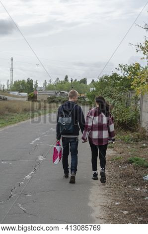 Heterosexual Couple Of Young People Are Walking Along The Road Holding Hands. Enamored Man And Woman