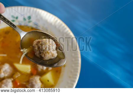 A Spoonful Of Soup With Meatballs On The Background Of A White Ceramic Plate. Portion Ready To Eat S