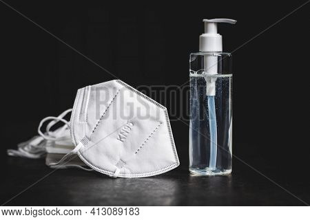 Coronavirus prevention hand sanitizer and kn95 respirator mask. Hand disinfectant gel in pump bottle on black table.