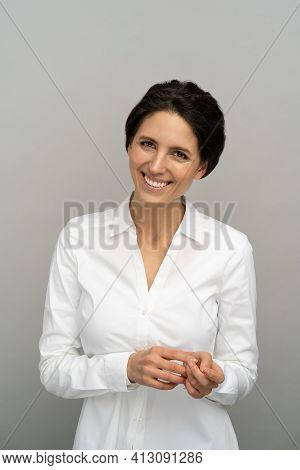 Shy Smiling Employee Or Business Woman With Perfect Teeth Smile, Isolated On Studio Grey Background.