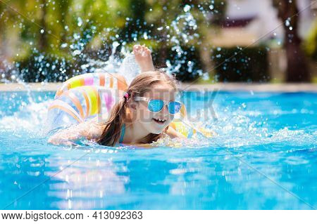 Child With Inflatable Toy Ring Float In Swimming Pool. Little Girl Learning To Swim And Dive In Outd
