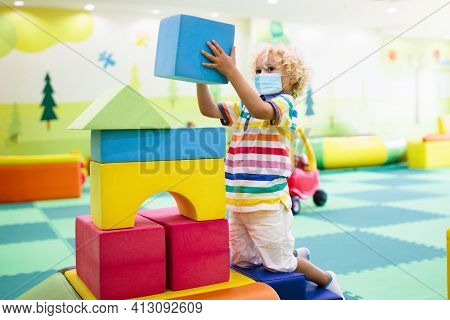 Child In Face Mask Playing With Colorful Construction Toy Blocks. Preschool And Kindergarten Kids In