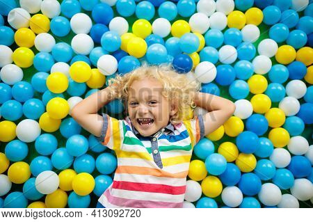 Child Playing In Ball Pit. Colorful Toys For Kids. Kindergarten Or Preschool Play Room. Toddler Kid