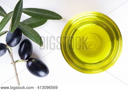 Bowl Of Glass Full Of Extra Virgin Olive Oil Made In Puglia, Salento On A White Table With Olive Bra