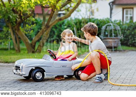 Two Happy Children Playing With Big Old Toy Car In Summer Garden, Outdoors. Kid Boy Refuel Car With