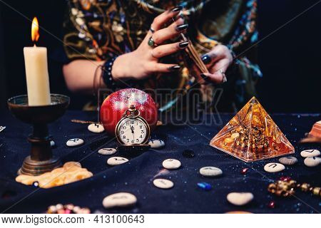 A Fortune Teller Shuffles Tarot Cards, Surrounded By Magical And Mysterious Objects. Hands Close-up.
