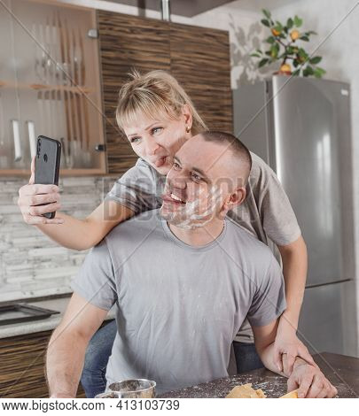A Young Couple In Love In The Kitchen Smeared In Flour Makes A Selfie On The Phone. He Makes A Face