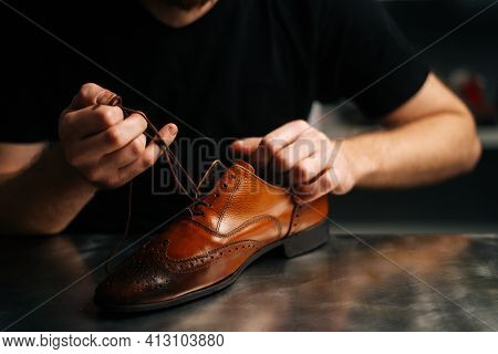 Close-up Hands Of Unrecognizable Male Shoemaker Tying Laces On Repaired And Polished Light Brown Lea