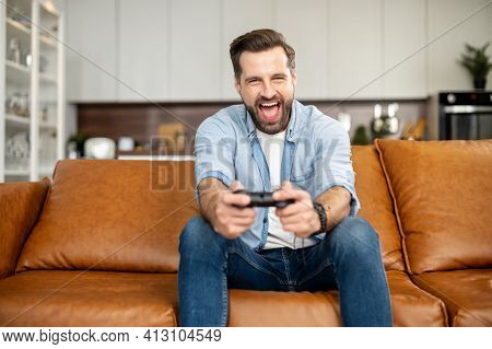Front View Of Young Bearded Hipster Man Sitting On The Couch In The Living Room Staying At Home And