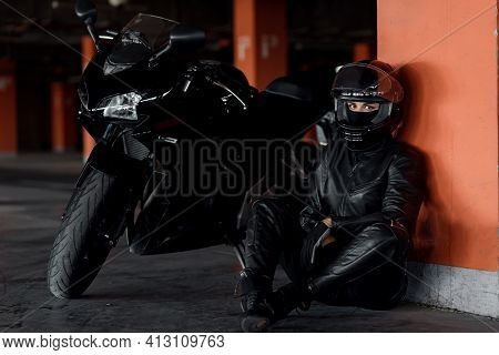 Stylish Young Woman Motorcycle Rider With Beautiful Eyes In Black Protective Gear And Full-face Helm