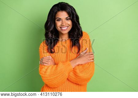 Photo Of Pretty Adorable Dark Skin Woman Wear Orange Sweater Embracing Herself Isolated Green Color