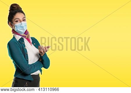 A Beautiful Flight Attendant In A Green Jacket And Mask In Front Of A Yellow Background. Perfect Sho