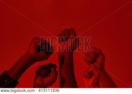 Raised Hands With Clenched Fists Of Multiracial People On Red Background. Stop Racism Concept