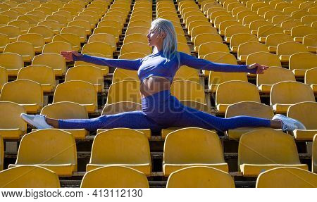 Sportive Woman In Split. Flexible Woman On Stadium Gym. Female Trainer Do Stretching Workout. Yoga C