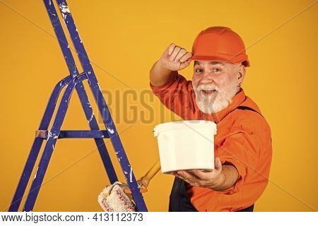 Senior Man Painter Use Roller On Ladder. Painting The Wall In Yellow. Professional Painter In Workin