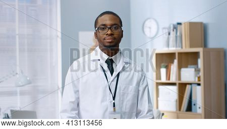Portrait Of African American Handsome Cheerful Positive Male Doctor In White Coat Standing In Cabine