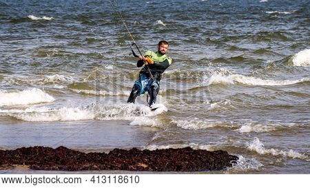 A Young Man Is Engaged In Extreme Kiteboarding In The Gulf Of Riga On October 21, 2020 At Cape Kolka