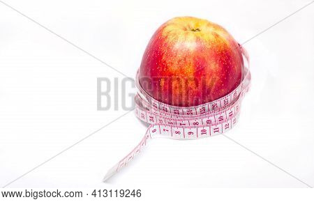 Juicy Red Apple And Measuring Tape Centimeter On White Background, Health Theme Of Proper Nutrition