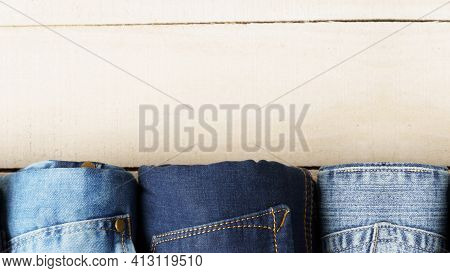Roll Up Frayed Blue Jeans On White Wood Background With Copy Space, Old Fashion Style Concept.