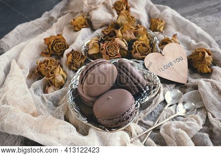 Set Of Different French Macaroons. Chocolate And Vanilla Macaroons With Dried Roses On A Wooden Tabl