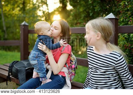 Two Big Sisters And Their Infant Brother Having Fun Outdoors. Two Young Girls Holding Their Baby Boy