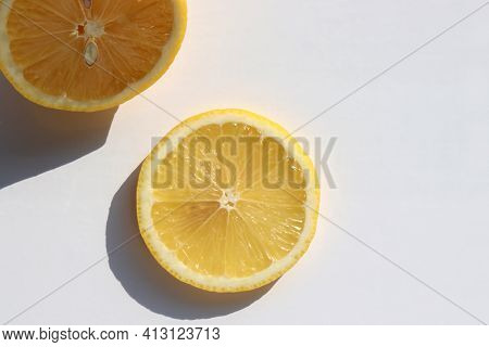 Close-up Of Lemon Fruit Cut In Half And Citrus Slice On White Table Background. Top View, Copy Space