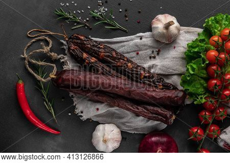 Bunch Of Red Dry Homemade Sausages On A Dark Background, Garlic And Sackcloth, Top View