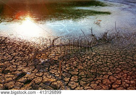 Lake Is At Low Water Levels . Drying Lake With Cracks On The Bottom . Climate Change , Extreme Weath