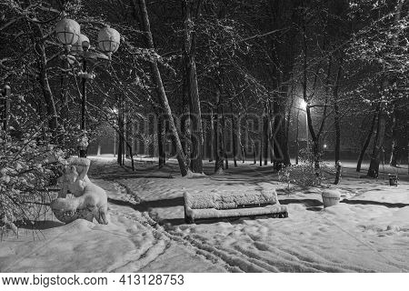 Winter Night In The Snowy Old Park.  Snow Covered Bench Among Snowy Trees. Winter Cityscape. Black A