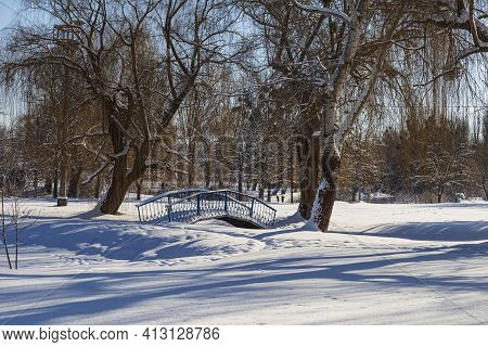 Landscape With Snow-covered City Park On A Bright Sunny Winter Day. Iron Footbridge Over A Frozen Ri