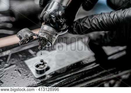 Close-up Photo Of Tattoo Master In Black Gloves Pouring Inks Into Plastic Cup.