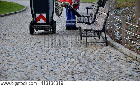 Square With Metal Benches In A Row. The Square Is Paved With Gray Granite Cubes. Cleaning The Park W