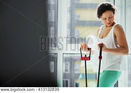 Athletic Woman Looking At Her Biceps While Exercising With A Fitness Harness During Daily Home Worko