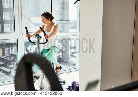 Young Woman Doing Morning Cardio Workout Exercising On Stationary Spin Bike
