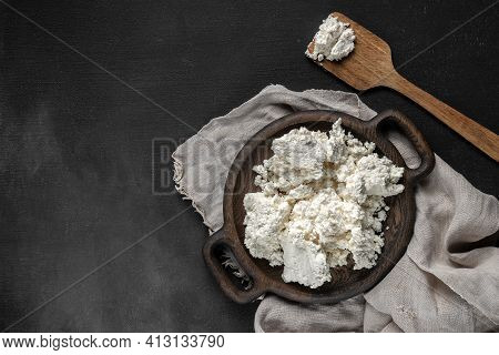 Fresh Cottage Cheese On A Wooden Plate With Spatula Top View. Dark Background With Gray Sackcloth, C