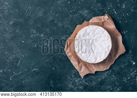 Round Camembert Cheese, Traditional Milk Creamy Dairy Product On Vintage Dark Background. Top View