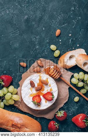 French Camembert Cheese Served On Grape, Honey, Almond, Strawberries, Baguette On Dark Background. T
