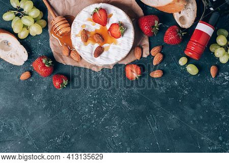 Camembert Cheese With Grape, Almond Nuts, Baguette, Strawberries, Honey, Wine On Rustic Dark Backdro