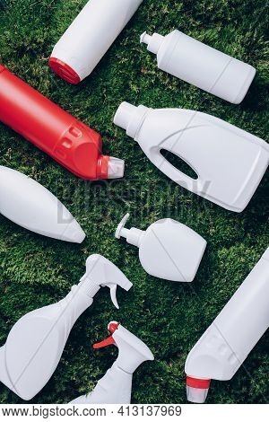 Cleaning Products On Green Grass, Moss Background. Top View. Copy Space. Chemical Cleaning Supplies.