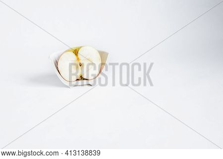 Sliced half Of An Apple In A Broken Half Of A Ceramic Small Plate On A White Background. Place For