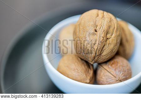 A Few Whole Walnuts In A Round-shaped Brown Shell Lie In A Small White Platter On Gray Plate On A Bl