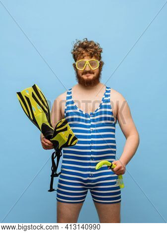 Funny Red-headed Man In Swimming Suit And Goggles Isolated On Blue Background.