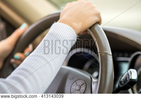 Close Up View Of Woman Holding Steering Wheel Driving A Car On City Street On Sunny Day.