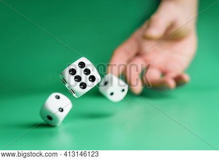 Hand Throws Dice On A Green Background With Selective Focus. Dice Close Up.