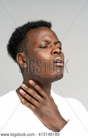 Black Man Touches Fingers Of Sore Throat, Thyroid Gland Isolated On Gray Background. Painful Swallow