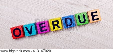 On A Light Wooden Background On Multi-colored Bright Wooden Cubes The Word Overdue