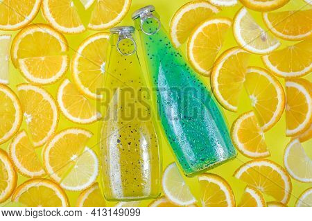 Two Glass Bottles On A Bright Tropical Citrus Background. Blue And Yellow Drinks With Seeds. Orange