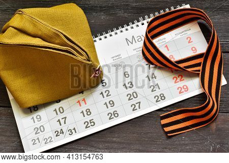 May 9. St. George Ribbon In The Form Of 9, Calendar And A Military Cap On A Wooden Background. The T