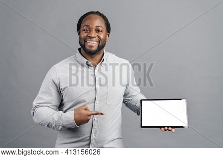 Hilarious African-american Young Man With Dreadlocks Holding A Digital Tablet And Point Finger At Bl